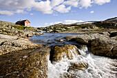 Rotes Holzhaus am Fluß im Nationalpark Hardangervidda, Rallarweg, Hordaland, Südnorwegen, Norwegen, Skandinavien; Spätsommer; Hochebene; Spätsommer; Fjell, Europa