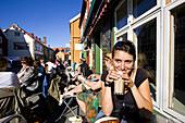 Junge Frau sitzt in einem Straßencafe und trinkt einen Milchkaffee, Stadtviertel Mollenberg, Trondheim, Trondelag, Mittelnorwegen, Norwegen, Skandinavien; Toristin, Europa