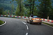 Convertible passing bendy road in the evening, Black Forest, Baden-Wuerttemberg, Germany