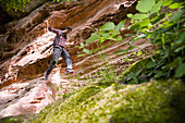Hiker jumping from rock, Wasigenstein, Alsace, France