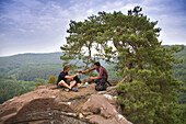 Two men having a picnic on sandston rock, Palatine Forest, Rhineland-Palentine, Germany