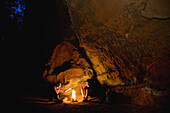 Two men enyoing a campfire near sandstone rock, Palatine Forest, Rhineland-Palentine, Germany