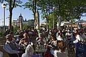 People sitting in a cafe, Jardines de las Vistillas, Catedral de Nuestra Senora de la Almudena in background, Fiestas de San Isidro Labrador, Madrid, Spain