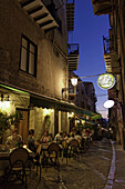 Guests sitting outside a restaurant in the evening, Cefalu, Sicily, Italy