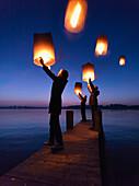 Three persons holding Sky lanterns, Lake Chiemsee, Bavaria, Germany