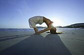 Young woman practicing yoga at beach, Majorca, Balearic Islands, Spain