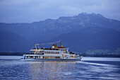 Passenger ferry on lake Chiemsee, mountain Kampenwand in background, Chiemgau, Bavaria, Germany