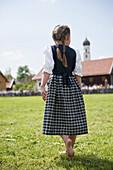 Barfoot girl wearing dirndl walking over meadow, May Running, Antdorf, Upper Bavaria, Germany
