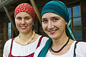 Portrait of two women in traditional costume welcoming the tourists to the museum of Russian wooden architecture of Kizhi, Lake Onega, Republic of Karelia, Russia