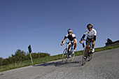 Two men on racing bikes on a coutry road in the sunlight, Marche, Italy, Europe