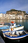 Cefalu, Sicily, Italy  Fishing harbor of the medieval town in late afternoon light  Boats tied to dock  Village and giant rock ´la rocca´ in background  province of Palermo