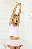 Young woman yawning and stretching in the morning