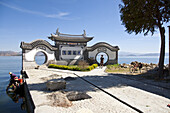 Moon gate at Erhai lake, traditional chinese architecture, tourist with bicycle, women doing the washing, Yunnan, People's Republic of China, Asia