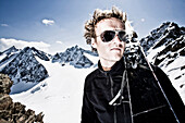 Young man with telemark-skis on shoulder in front of Oestlicher Seespitze, Westlicher Seespitze and Ruderhofspitze, Wildgratscharte, Stubaier Alpen, Tirol, Austria, MR