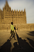 Laughing boy in front of the mosque of Djenna, Mali, Africa