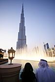 Traditional couple at the Dubai Fountain in the evening, Burj Khalifa, Burj Chalifa, Dubai, UAE, United Arab Emirates, Middle East, Asia