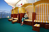 Beach chair with figure aboard AIDA Bella cruiser in the evening