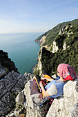 Woman with climbing gear looking towards the steep coast at the Mediterranean, natural park Porto Venere, national park Cinque Terre, UNESCO world heritage site, Liguria, Italy