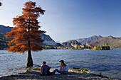 Couple on the lake shore, View from Isola Bella towards Isola Superiore o dei Pescatori, Lago Maggiore, Piedmont, Italy