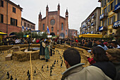 People fishing for wine bottles for a prize during the Palio di Alba festival, cathedral in the background, Piazza Risorgimento, Piedmont, Italy