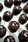 Chocolate-covered marshmallows decorated to look like ghosts for Halloween.