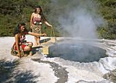Maori women cooking food in hot pool Whakarewarewa Rotorua New Zealand