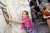 Young girl inserts her hand over a handprint, Station V, Way of the cross, Via Dolorosa, Jerusalem, Israel, Middle East