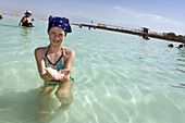 Young girl in the Dead Sea holding sea salt in her hand, En Bokek, Israel, Middle East