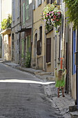 Girl wearing a green dress in the street in Valensole, Provence, France, Europe