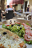 Dish with salad and people at a street cafe, Orange, Provence, France, Europe