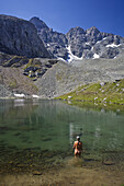 Naked woman bathing in lake Lai Neir, Val Bercla, Piz Platta in background, Canton of Grisons, Switzerland