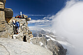 Mountaineer reaching summit of Gran Paradiso, Gran Paradiso National Park, Aosta Valley, Italy