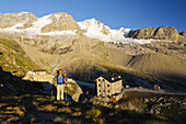 Man hiking, mountain hut Rifugio Chabod and Gran Paradiso in background, Gran Paradiso National Park, Aosta Valley, Italy