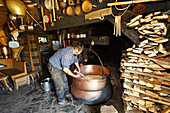 A man making cheese, traditional caseation on Alp Lapisa, Val d'Illiez, Valais, Switzerland
