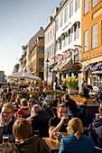 People sitting at waterfront along the Nyhavn Canal, Copenhagen, Denmark