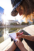 Woman writing a postcard, La Defense, Paris, France