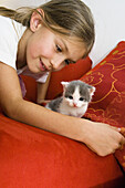 Girl with young domestic cat, Bavaria, Germany