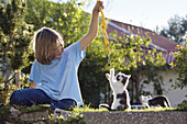 Girl playing with young domestic cat, kitten in the garden, Germany