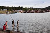 Boys playing in the water in front of the village Norrfaellsviken, Höga Kusten, Sweden, Europe