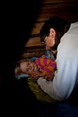 Mother saying good night to a girl in a cottage, national park Skuleskogen, Höga Kusten, Vaesternorrland, Sweden, Europe