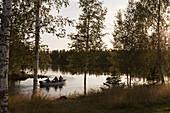 Drei Männer fahren morgens in einem kleinen Boot zum Angeln, Västerbotten, Schweden, Europa