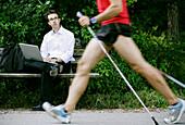 Businessman using a laptop, Nordic Walker passing