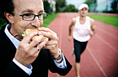 Businessman eating a burger, runner in background