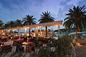 Bars und Restaurants an der Promenade von Hvar in der Daemmerung, Kroatien