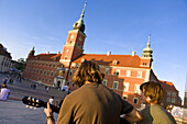 Young men playing guitar in front of Royal Castle at Castle Square, Warsaw, Poland, Europe