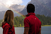 Young couple watching rainbow, lake Lautersee, Mittenwald, Werdenfelser Land, Upper Bavaria, Germany