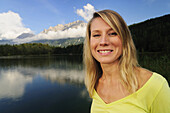 Young woman smiling at camera, lake Lautersee, Mittenwald, Werdenfelser Land, Upper Bavaria, Germany