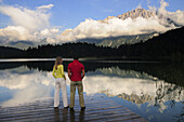 Couple standing on jetty, lake Lautersee, Mittenwald, Werdenfelser Land, Upper Bavaria, Germany