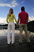 Couple holding hands on a jetty, lake Lautersee, Mittenwald, Werdenfelser Land, Upper Bavaria, Germany