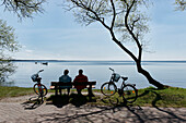 Couple having a rest along the lake shore, Klink, Mueritz, Mecklenburg lake District, Mecklenburg-Western Pomerania, Germany